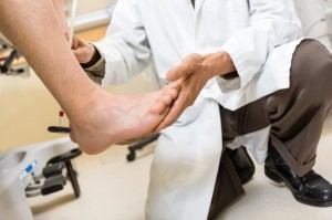 Doctor Examining Patient's Foot In Hospital